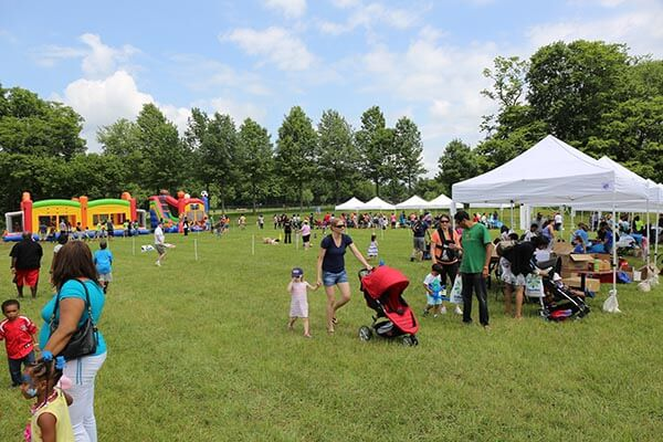 image of kids day event. People standing and walking in the park.