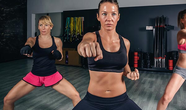 Group of beautiful women in a hard boxing class on gym training punch