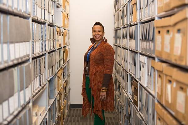 Lela Sewell Standing in library