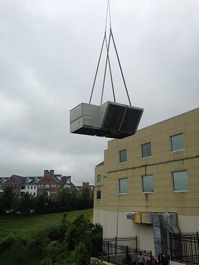 ac unit being lifted by a crane