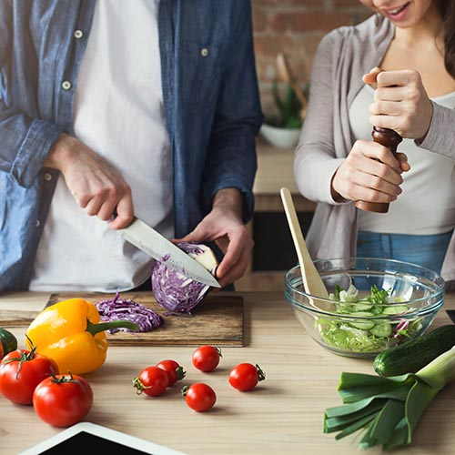 Closeup of couple cooking healthy food together in their loft kitchen at home. Preparing vegetable salad.
